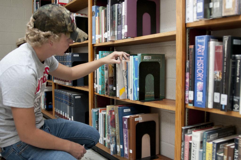 Student getting a book off a shelf.