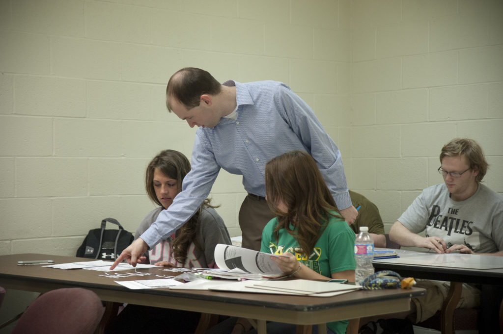 Professor helping students inside of a classroom.