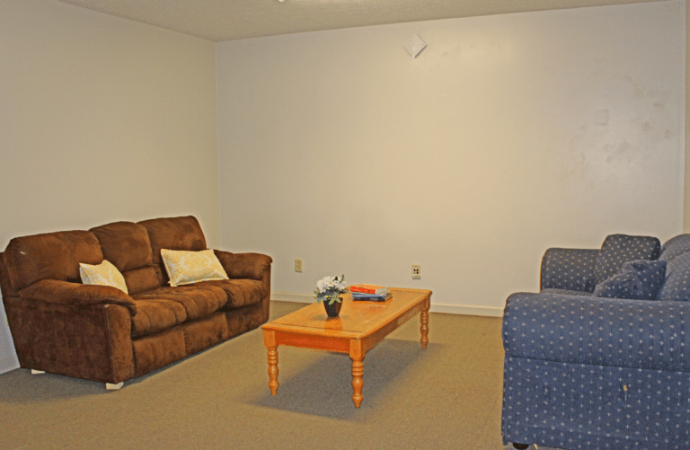 The living room of an apartment in Young Hall. There are two couches and a coffee table.