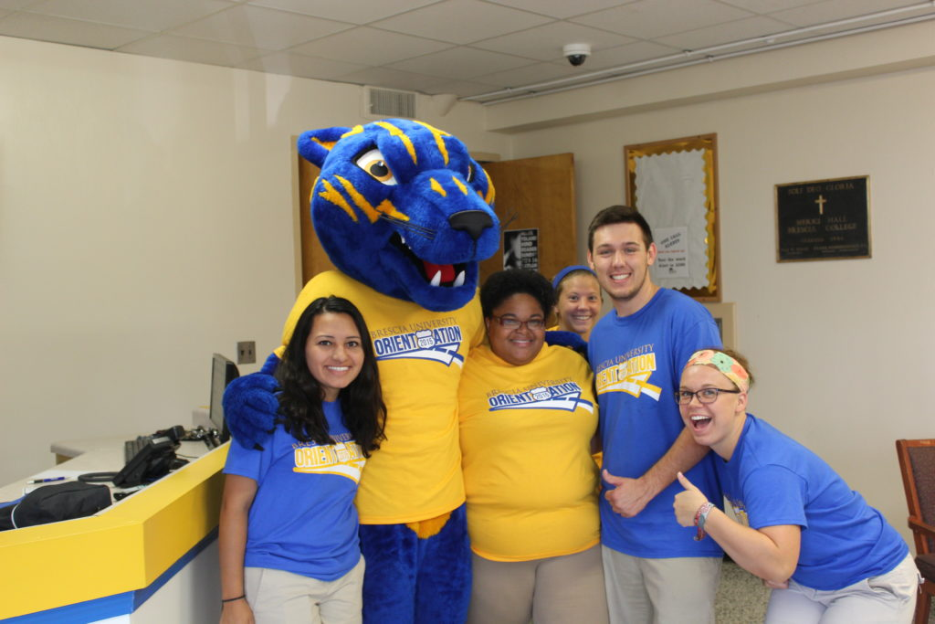 Four students gather around the Brescia University mascot, Barney the Bearcat, inside the lobby of a residence hall.
