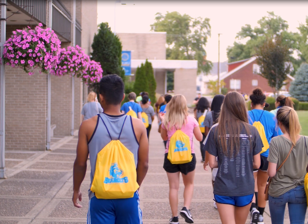 Group of students walking outside of the Moore Center in the Quad.